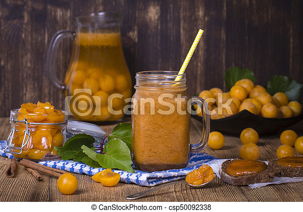 Yellow plum smoothie in glass, lemonade, jam and ripe yellow plum on wooden table. Bio healthy food and drink - csp50092338