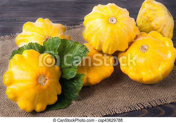 yellow squash on a wooden background with napkin of burlap - csp43629788