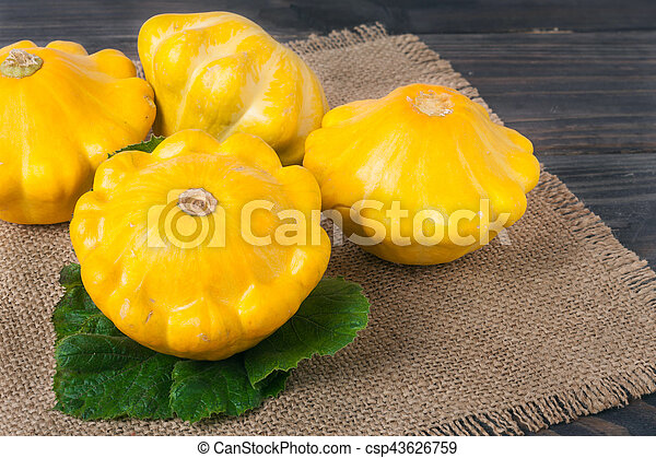 yellow squash on a wooden background with napkin of burlap - csp43626759
