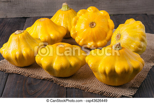 yellow squash on a wooden background with napkin of burlap - csp43626449
