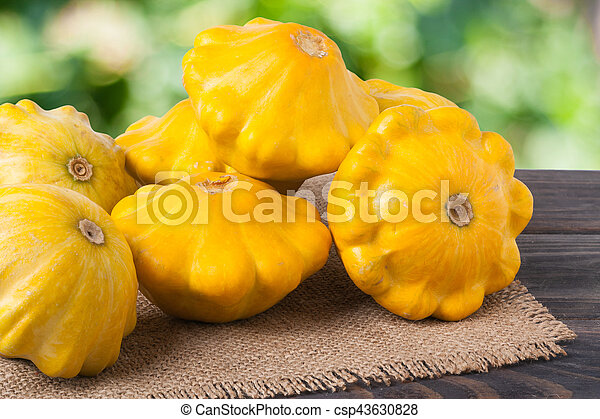 yellow squash on a wooden table with napkin of burlap and blurred green background - csp43630828