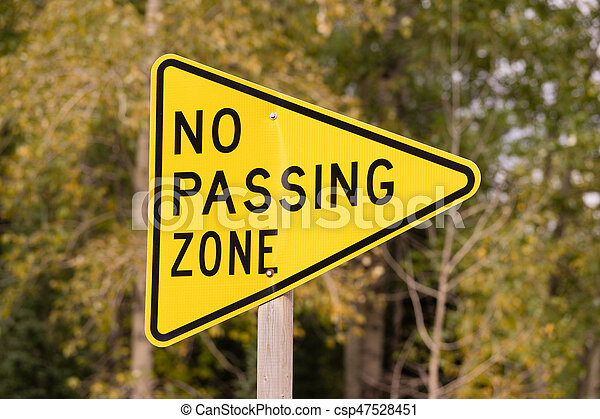 Yellow triangle road sign warning no passing zone. A ...