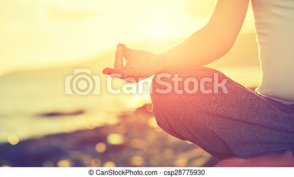 yoga concept hand woman practicing lotus pose on beach