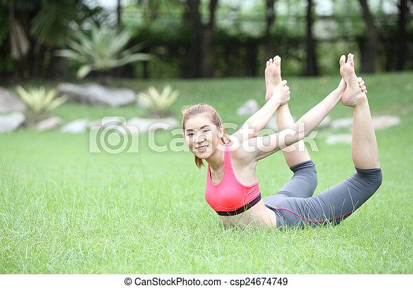 yoga dhanurasana bow poseasian woman on lawn