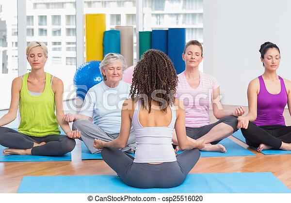 Gente practicando posición de loto en clase de yoga - csp25516020