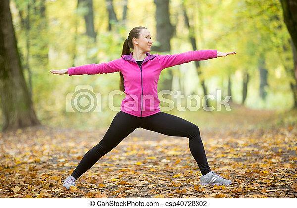 Yoga outdoors: Warrior Two pose - csp40728302