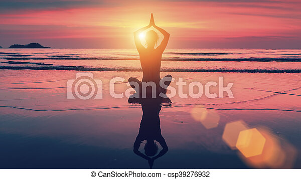 silhouette yoga woman in lotus pose on beach during sunset