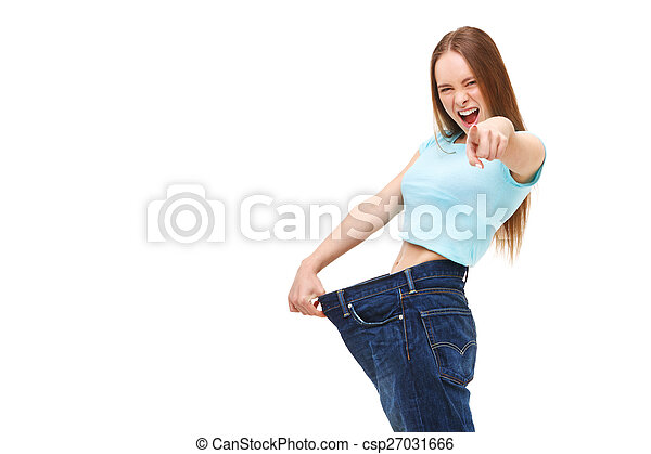 You can do it! Young slim woman with large jeans pointing finger - csp27031666