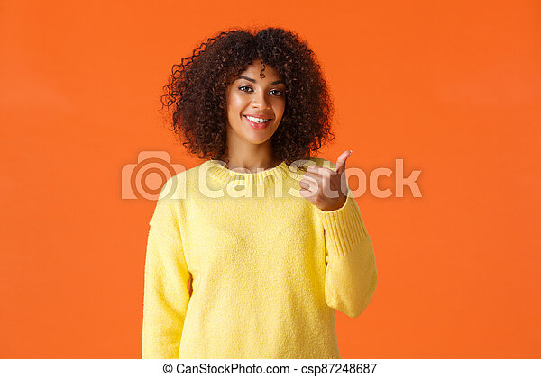 You should come and see it. Carefree good-looking hipster woman yellow sweater, inviting come inside pointing thumb behind herself and smiling, recommend product or company service, orange background - csp87248687