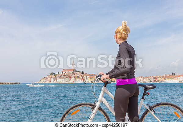 Young active woman cycling round Rovinj, Istria, Croatia. - csp44250197