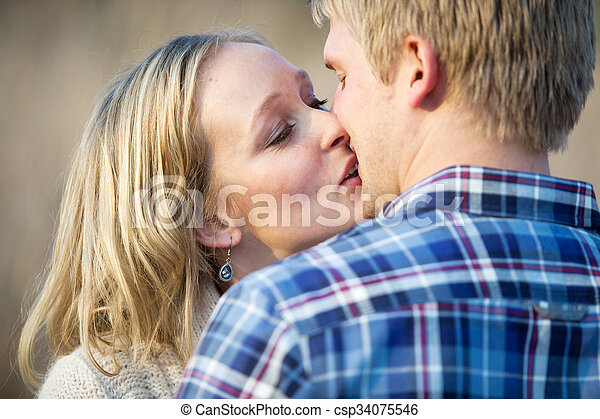Young adult couple kissing outside in daytime - csp34075546