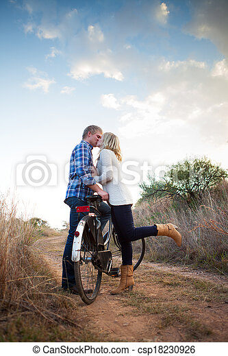 Young adult couple with old bicycle kissing - csp18230926