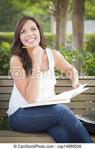 Young Adult Female Student on Bench Outdoors - csp14889526