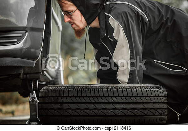 Young adult inspecting the wheel of a car - csp12118416
