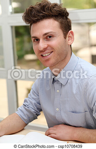 Young adult man writing note - csp10708439
