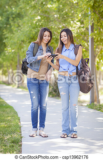 Young Adult Mixed Race Twin Sisters Sharing Cell Phone Experience Outside. - csp13962176
