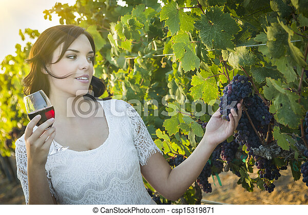 Young Adult Woman Enjoying A Glass of Wine in Vineyard - csp15319871