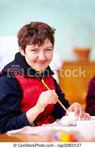 young adult woman with disability engaged in craftsmanship in rehabilitation center - csp32803127