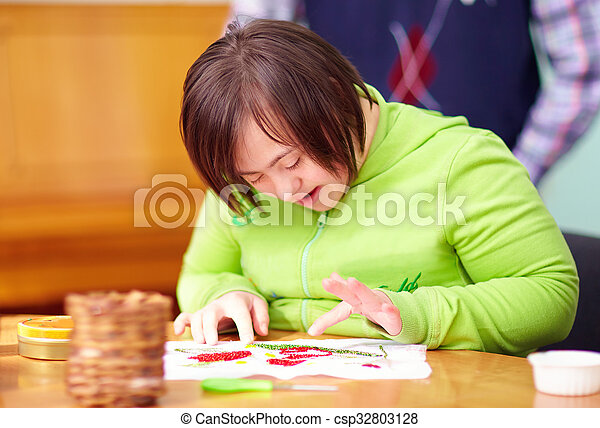 young adult woman with disability engaged in craftsmanship in rehabilitation center - csp32803128