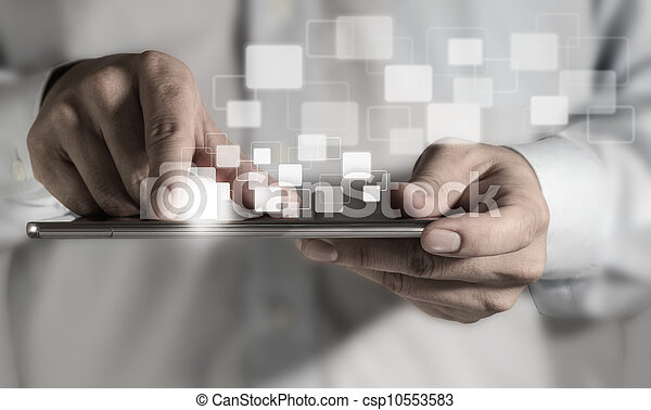 Young adult working on a digital tablet - csp10553583