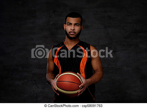 Young African-American basketball player in sportswear isolated over dark background. - csp58091763