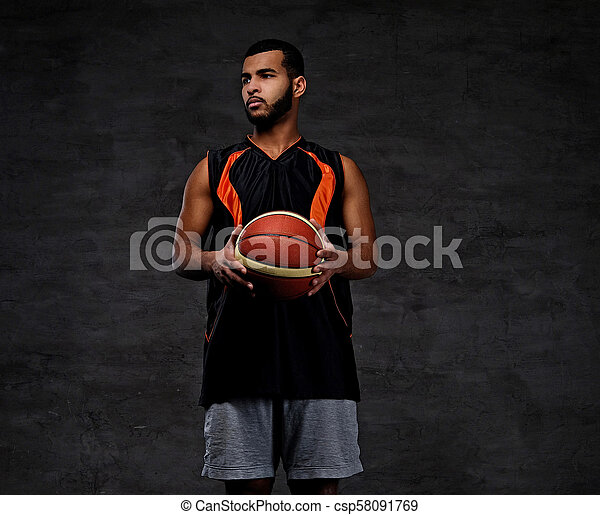 Young African-American basketball player in sportswear isolated over dark background. - csp58091769