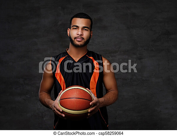 Young African-American basketball player in sportswear isolated over dark background. - csp58259064