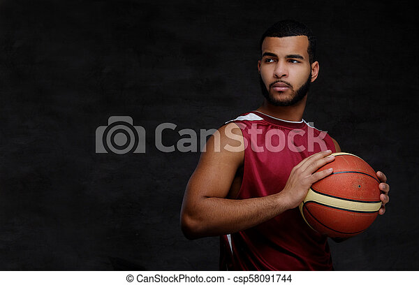 Young African-American basketball player in sportswear isolated over dark background. - csp58091744