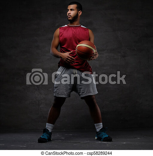 Young African-American basketball player in sportswear playing with ball. Isolated on a dark background. - csp58289244