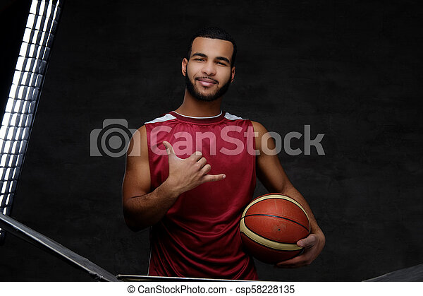 Young African-American basketball player in sportswear isolated over dark background. - csp58228135