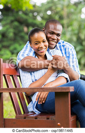 young african american couple sitting at the park - csp19811445