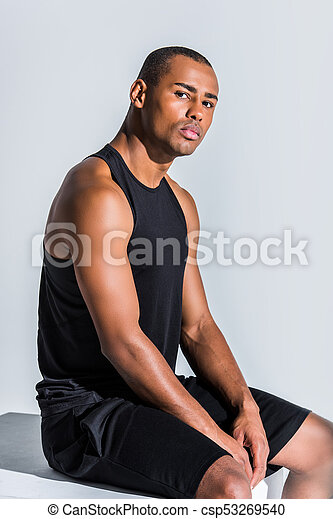 young african american sportsman sitting and looking at camera on grey - csp53269540