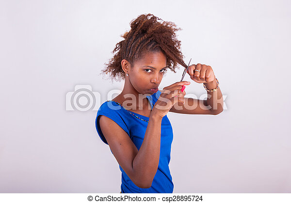 Young African American woman cutting her frizzy afro hair with scissors - Black people - csp28895724