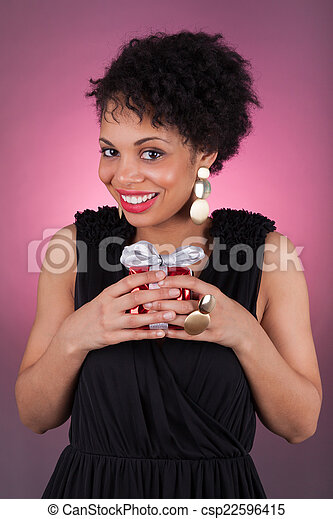 Young African American woman holding a gift - csp22596415