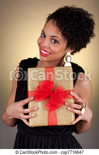 Young African American woman holding a gift - csp7716647