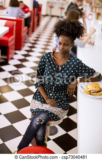 Young african american woman in the diner - csp73040481