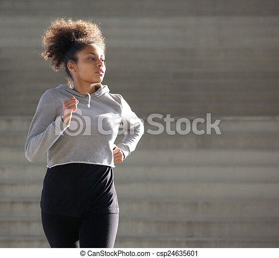 Young african american woman jogging outdoors - csp24635601