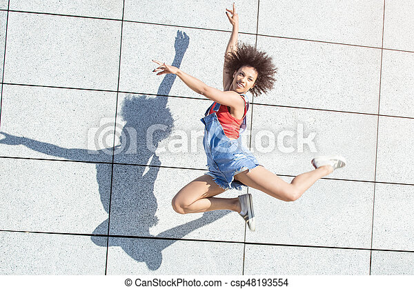 Young african american woman jumping. - csp48193554