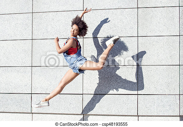 Young african american woman jumping. - csp48193555