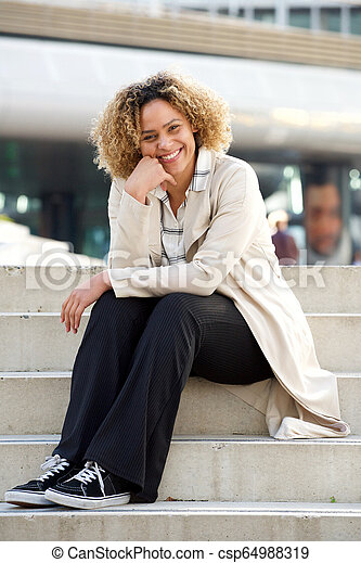 young african american woman sitting on steps in city - csp64988319