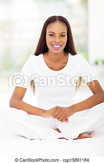 young african american woman sitting on bed - csp15891184