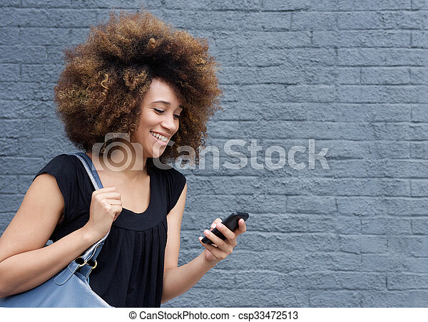 Young african american woman smiling with cellphone - csp33472513
