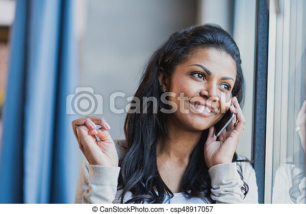 young african american woman with smartphone near the window at home - csp48917057
