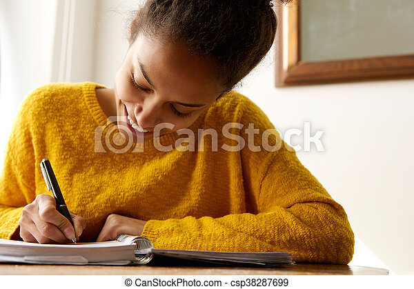 Young african american woman writing in book - csp38287699
