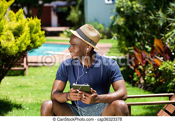 Young african american man with hat sitting outdoors listening to music with digital tablet