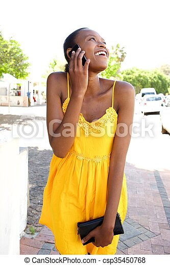 Young african woman in summer dress talking on cell phone - csp35450768