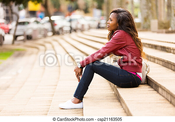 young african woman sitting outdoors - csp21163505