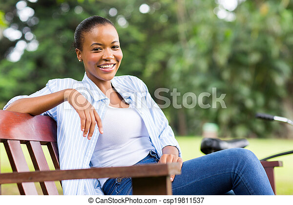 young african woman sitting outdoors - csp19811537