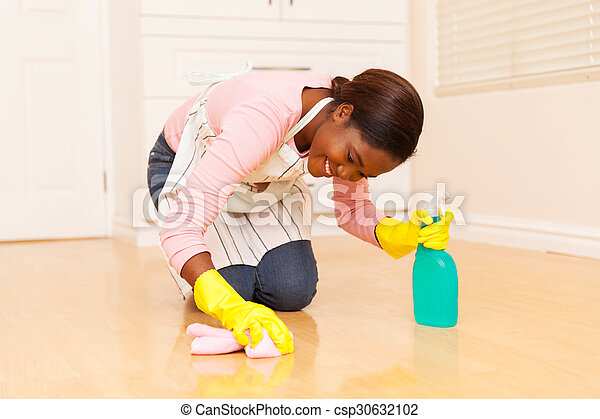 young african woman wiping wooden floor - csp30632102
