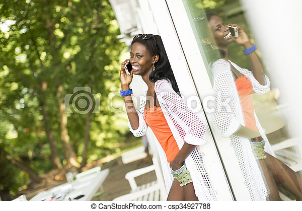 Young african woman with mobile phone - csp34927788